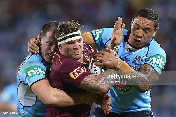Josh McGuire of the Maroons is tackled by Paul Gallen and Tyson Frizell of the Blues during game two of the State Of Origin series between the...