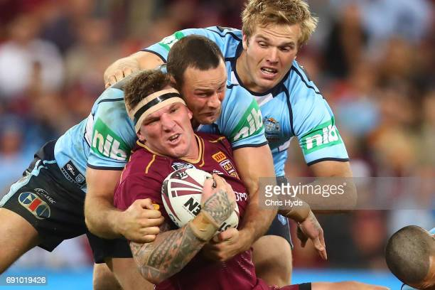 Josh McGuire of the Maroons is tackled during game one of the State Of Origin series between the Queensland Maroons and the New South Wales Blues at...