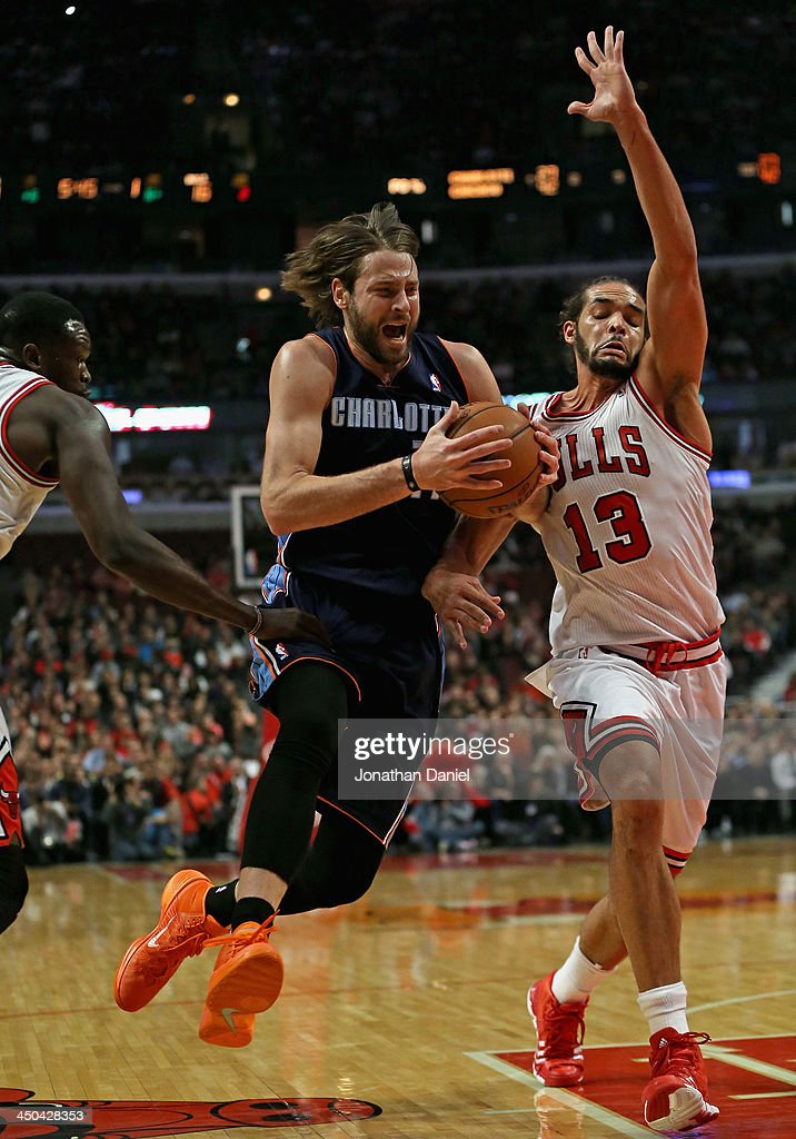 Josh McRoberts #11 of the Charlotte Bobcats drives between Loul Deng #9 (L) and Joakim Noah #13 of the Chicago Bulls at the United Center on November 18, 2013 in Chicago, Illinois.