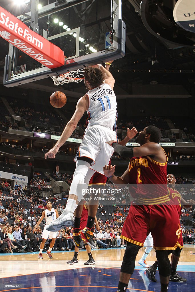 Josh McRoberts #11 of the Charlotte Bobcats dunks against Kyrie Irving #2 of the Cleveland Cavaliers at the Time Warner Cable Arena on April 17, 2013 in Charlotte, North Carolina.