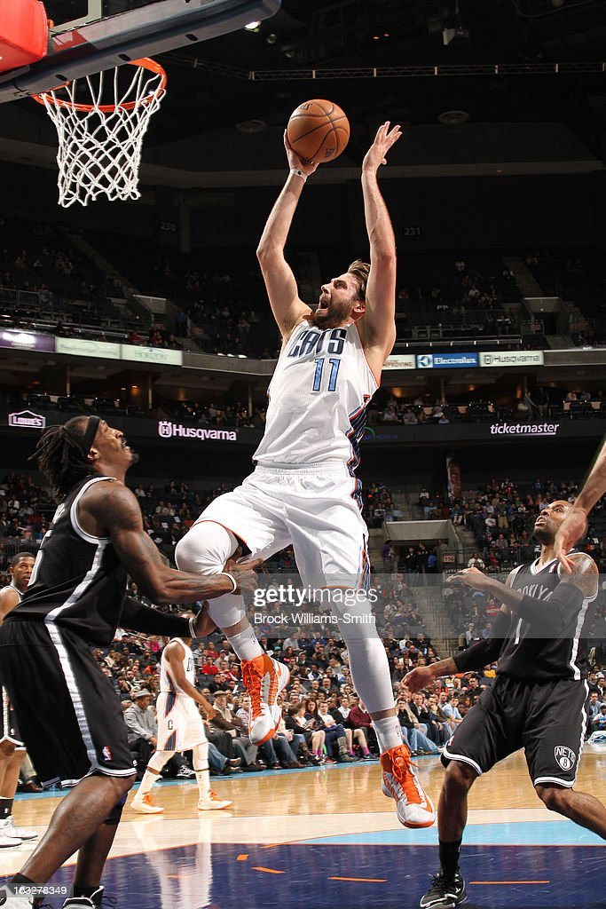 Josh McRoberts #11 of the Charlotte Bobcats goes to the basket against Gerald Wallace #45 of the Brooklyn Nets at the Time Warner Cable Arena on March 6, 2013 in Charlotte, North Carolina.