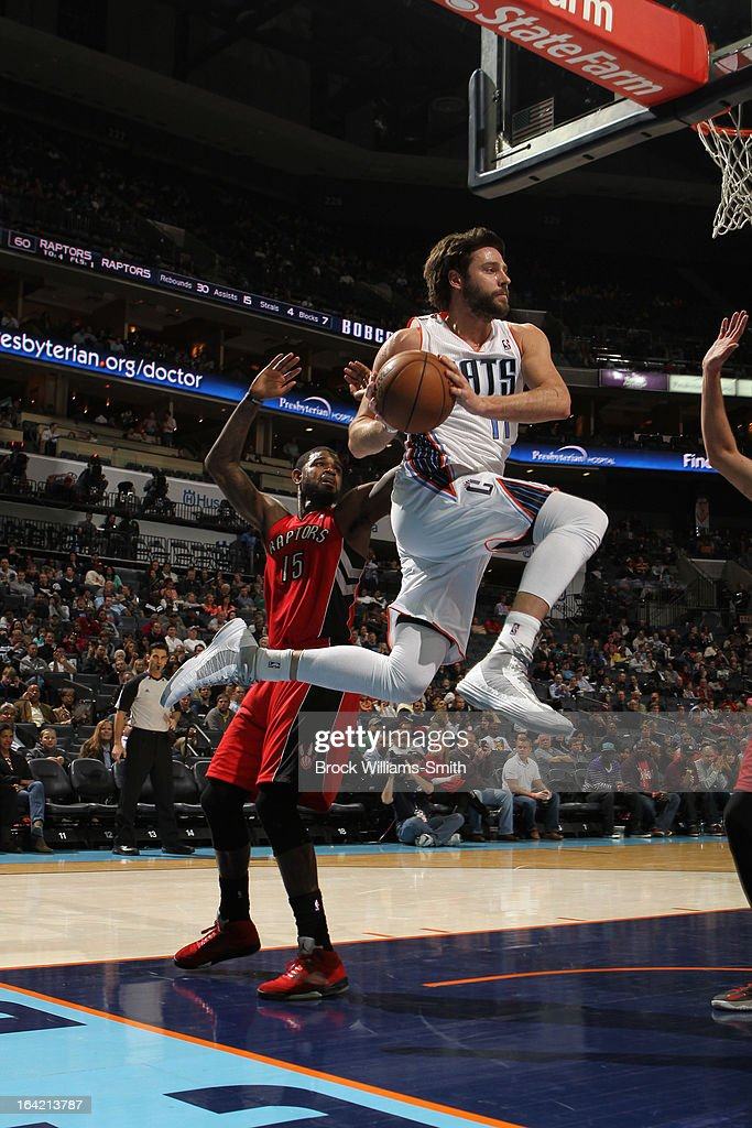 Josh McRoberts #11 of the Charlotte Bobcats passes the ball against Amir Johnson #15 of the Toronto Raptors at the Time Warner Cable Arena on March 20, 2013 in Charlotte, North Carolina.