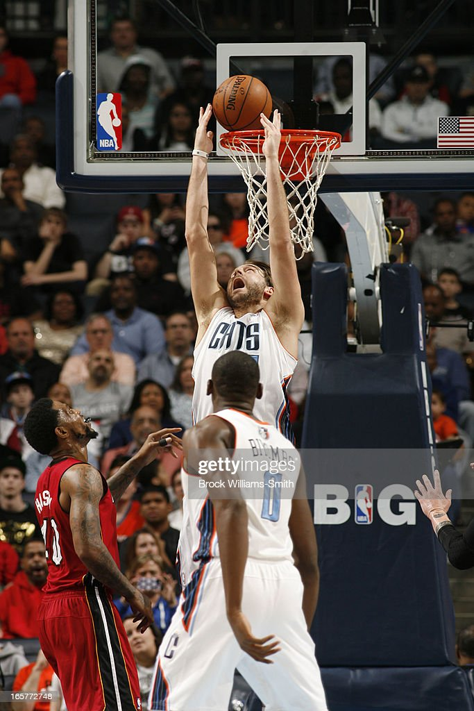 Josh McRoberts #11 of the Charlotte Bobcats reverse dunks against Udonis Haslem #40 of the Miami Heat at the Time Warner Cable Arena on April 5, 2013 in Charlotte, North Carolina.