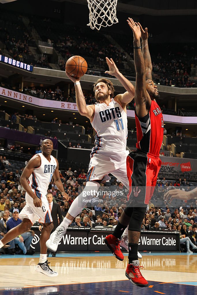 Josh McRoberts #11 of the Charlotte Bobcats shoots against Amir Johnson #15 of the Toronto Raptors at the Time Warner Cable Arena on March 20, 2013 in Charlotte, North Carolina.