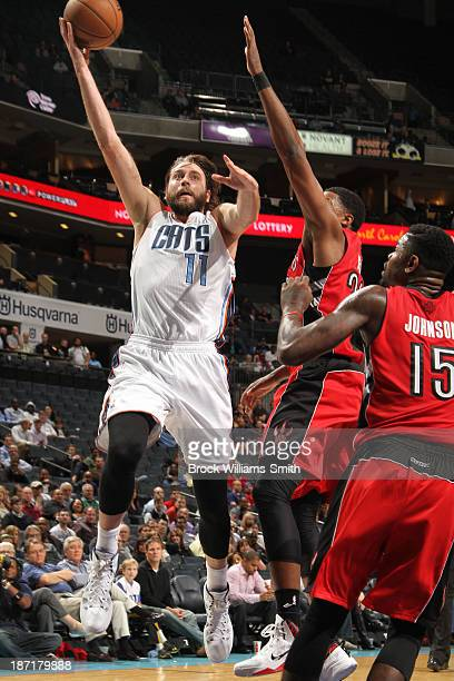 Josh McRoberts of the Charlotte Bobcats shoots against Amir Johnson of the Toronto Raptors during the game at the Time Warner Cable Arena on November...