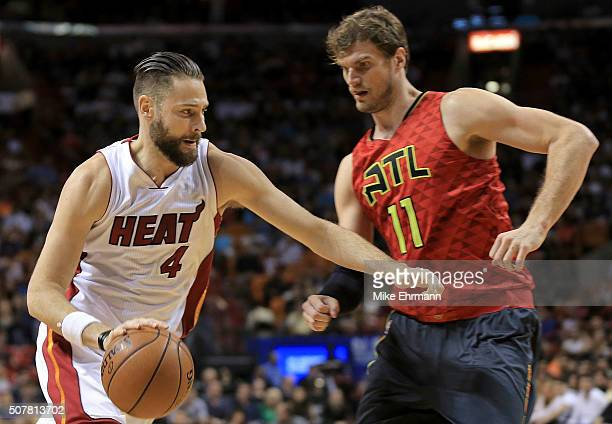 Josh McRoberts of the Miami Heat drives on Tiago Splitter of the Atlanta Hawks during a game at American Airlines Arena on January 31 2016 in Miami...