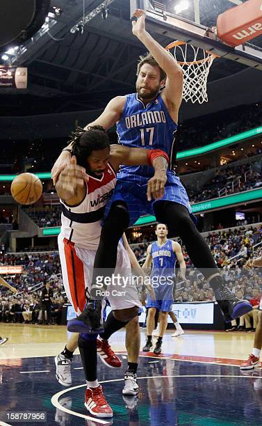 Josh McRoberts of the Orlando Magic fouls Nenê of the Washington Wizards during the second half at Verizon Center on December 28 2012 in Washington...