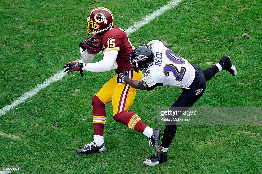 Josh Morgan #15 of the Washington Redskins avoids the tackle of Ed Reed #20 of the Baltimore Ravens during the first half at FedExField on December 9, 2012 in Landover, Maryland.