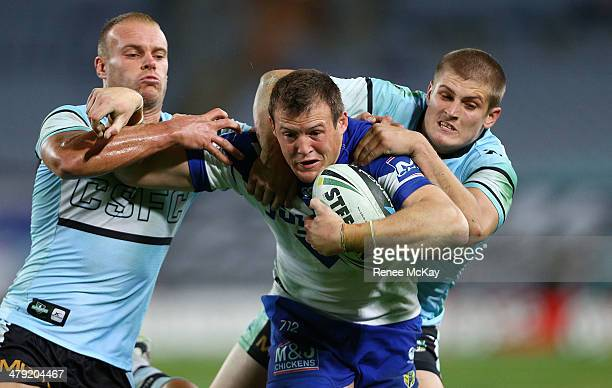 Josh Morris of the Bulldogs is tackled by Daniel Holdsworth and Blake Ayshford during the round two NRL match between the CanterburyBankstown...