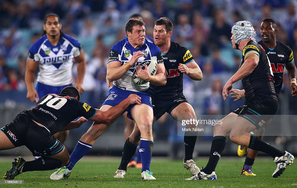 Josh Morris of the Bulldogs is tackled during the round 25 NRL match between the Canterbury Bulldogs and the Penrith Panthers at ANZ Stadium on August 31, 2013 in Sydney, Australia.