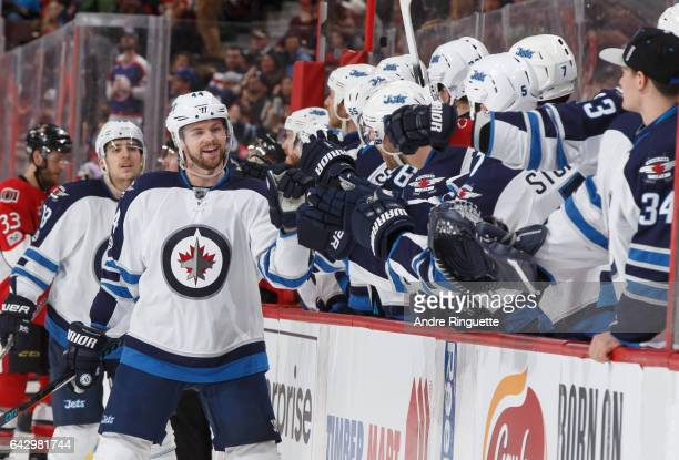 Josh Morrissey of the Winnipeg Jets celebrates his third period goal against the Ottawa Senators with teammates at the players bench at Canadian Tire...