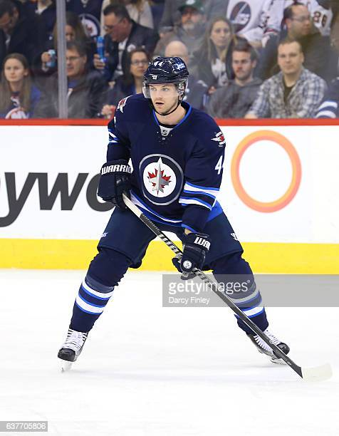 Josh Morrissey of the Winnipeg Jets keeps an eye on the play during first period action against the New York Islanders at the MTS Centre on December...