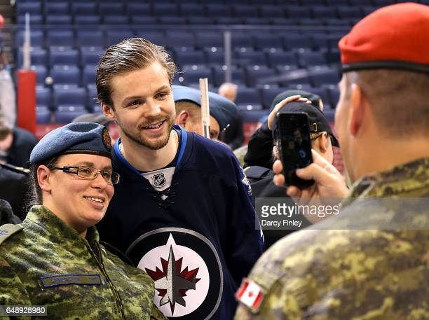 Josh Morrissey of the Winnipeg Jets poses with a member of the Canadian Armed Forces following NHL action between the Jets and the San Jose Sharks on...