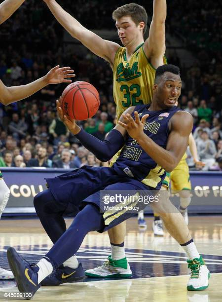 Josh Okogie of the Georgia Tech Yellow Jackets falls backwards while trying to pass the ball off as Steve Vasturia of the Notre Dame Fighting Irish...