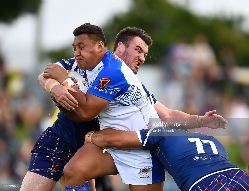 Josh Papalii of Samoa is tackled by Luke Douglas and Frankie Mariano of Scotland of Scotland during the 2017 Rugby League World Cup match between Samoa and Scotland at Barlow Park on November 11, 2017 in Cairns, Australia.