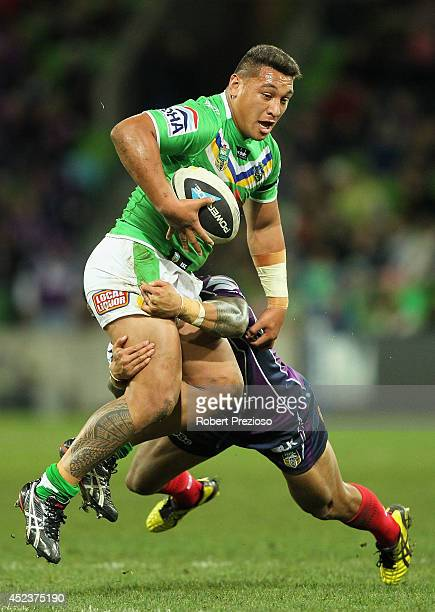 Josh Papalii of the Raiders is tackled by Ben Roberts of the Storm during the round 19 NRL match between the Melbourne Storm and the Canberra Raiders...