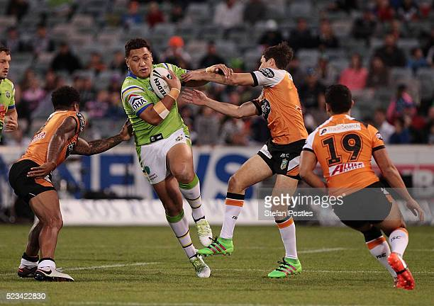 Josh Papalii of the Raiders is tackled during the round eight NRL match between the Canberra Raiders and the Wests Tigers at GIO Stadium on April 23...