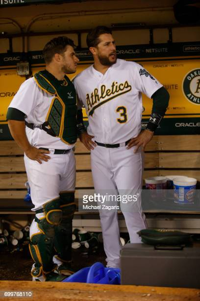 Josh Phegley and Trevor Plouffe of the Oakland Athletics talk in the dugout during the game against the Toronto Blue Jays at the Oakland Alameda...