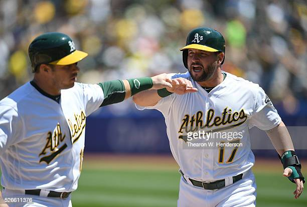 Josh Phegley and Yonder Alonso of the Oakland Athletics celebrates after they both scored against the Houston Astros in the bottom of the second...