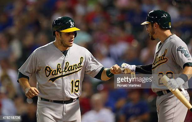 Josh Phegley of the Oakland Athletics celebrates with Eric Sogard after scoring against the Texas Rangers in the sixth inning at Globe Life Park in...