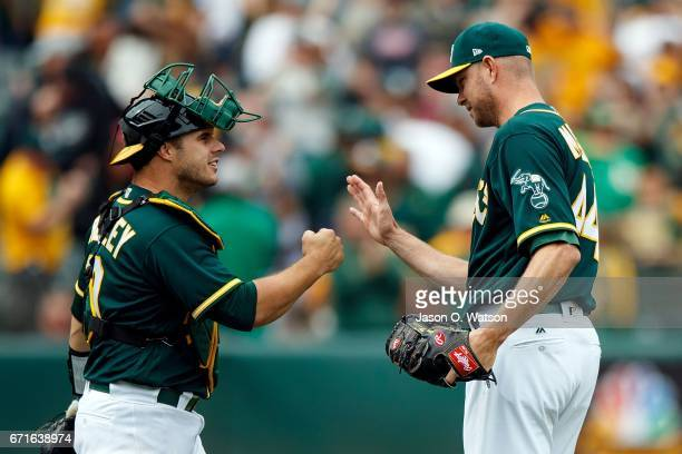 Josh Phegley of the Oakland Athletics celebrates with Ryan Madson after the game against the Seattle Mariners at the Oakland Coliseum on April 22...
