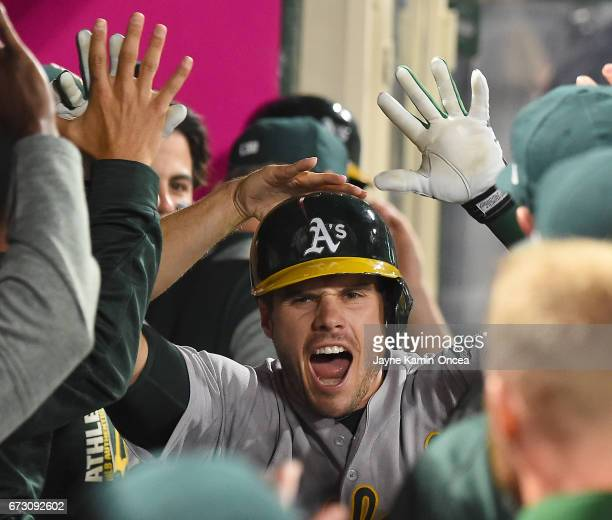 Josh Phegley of the Oakland Athletics is greeted in the dugout after a solo home run in the tenth inning of the game against the Los Angeles Angels...
