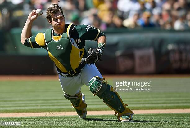 Josh Phegley of the Oakland Athletics looks to throw to first base against the Houston Astros in the top of the fifth inning at Oco Coliseum on...