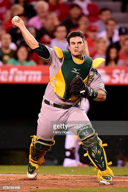 Josh Phegley of the Oakland Athletics makes a throw to first against the Los Angeles Angels at Angel Stadium of Anaheim on June 13 2015 in Anaheim...