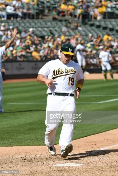 Josh Phegley of the Oakland Athletics scores against the Texas Rangers in the bottom of the fifth inning at Oakland Alameda Coliseum on September 24...