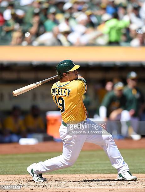 Josh Phegley of the Oakland Athletics swings and watches the flight of his ball as he hits a tworun homer against the Los Angeles Angels of Anaheim...