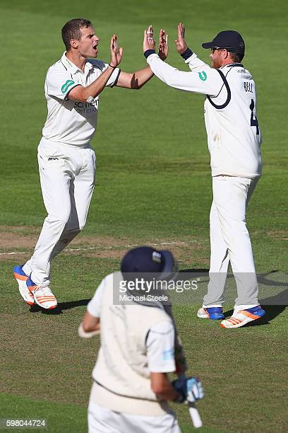 Josh Poysden of Warwickshire celebrates with Ian Bell after taking the wicket of Stephen Eskinazi of Middlesex during day one of the Specsavers...