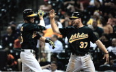 Josh Reddick and Brandon Moss of the Oakland Athletics celebrate after Reddick hit a tworun home run in the eighth inning against the Houston Astros...