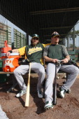Josh Reddick and Brandon Moss of the Oakland Athletics relax outside the batting cage prior to a spring training game against the Milwaukee Brewers...