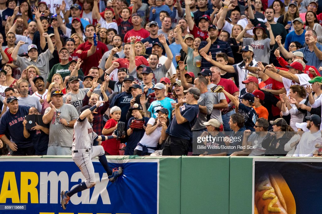 Josh Reddick #22 of the Boston Red Sox climbs the wall while attempting to catch a home run hit by Jackie Bradley Jr. #19 of the Boston Red Sox during the seventh inning of game three of the American League Division Series on October 8, 2017 at Fenway Park in Boston, Massachusetts.
