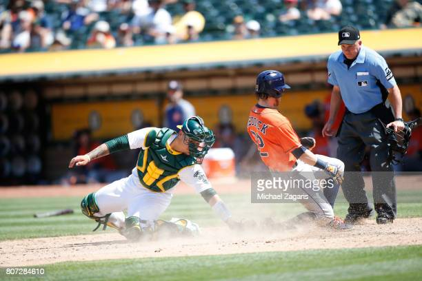 Josh Reddick of the Houston Astros avoids the tag by Bruce Maxwell of the Oakland Athletics to slide safely into home during the game at the Oakland...