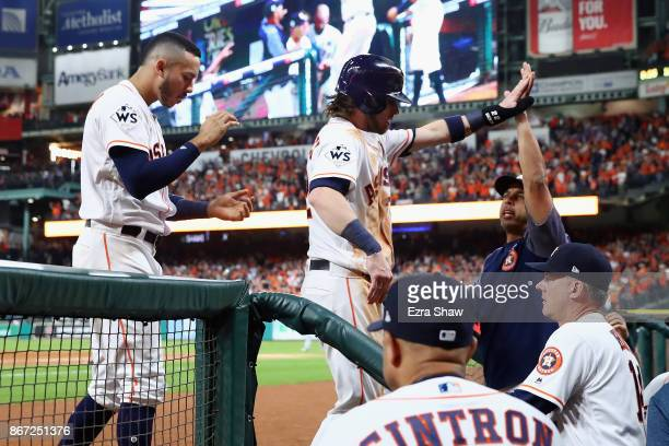 Josh Reddick of the Houston Astros celebrates with teammates after scoring during the fifth inning against the Los Angeles Dodgers in game three of...