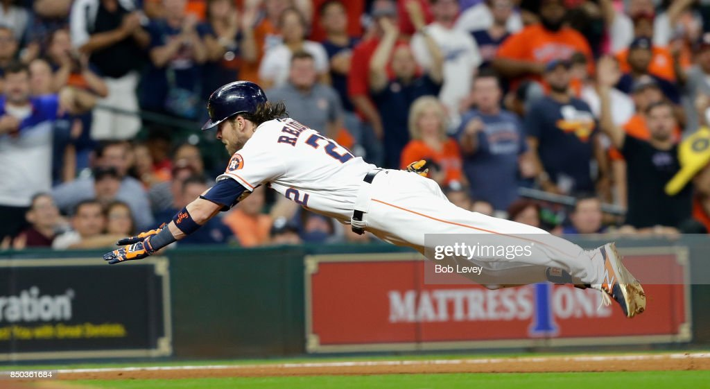 Josh Reddick #22 of the Houston Astros dives into third base for a triple in the seventh inning against the Chicago White Sox at Minute Maid Park on September 20, 2017 in Houston, Texas.