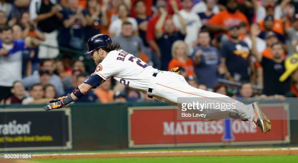 Josh Reddick of the Houston Astros dives into third base for a triple in the seventh inning against the Chicago White Sox at Minute Maid Park on...