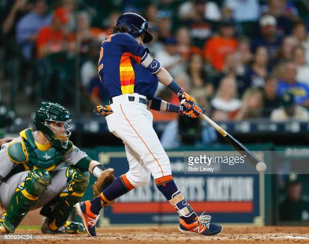 Josh Reddick of the Houston Astros grounds out in the fourth inning as Dustin Garneau of the Oakland Athletics looks on at Minute Maid Park on August...