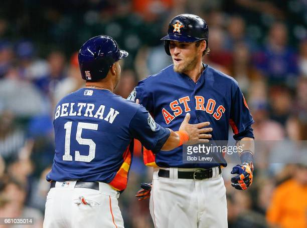 Josh Reddick of the Houston Astros receives congratulations from Carlos Beltran after hitting a home run in the second inning against the Chicago...