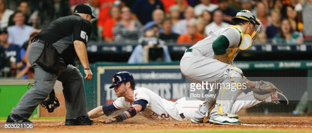 Josh Reddick of the Houston Astros scores as he slides past Bruce Maxwell of the Oakland Athletics in the sixth inning as home plate umpire Eric...