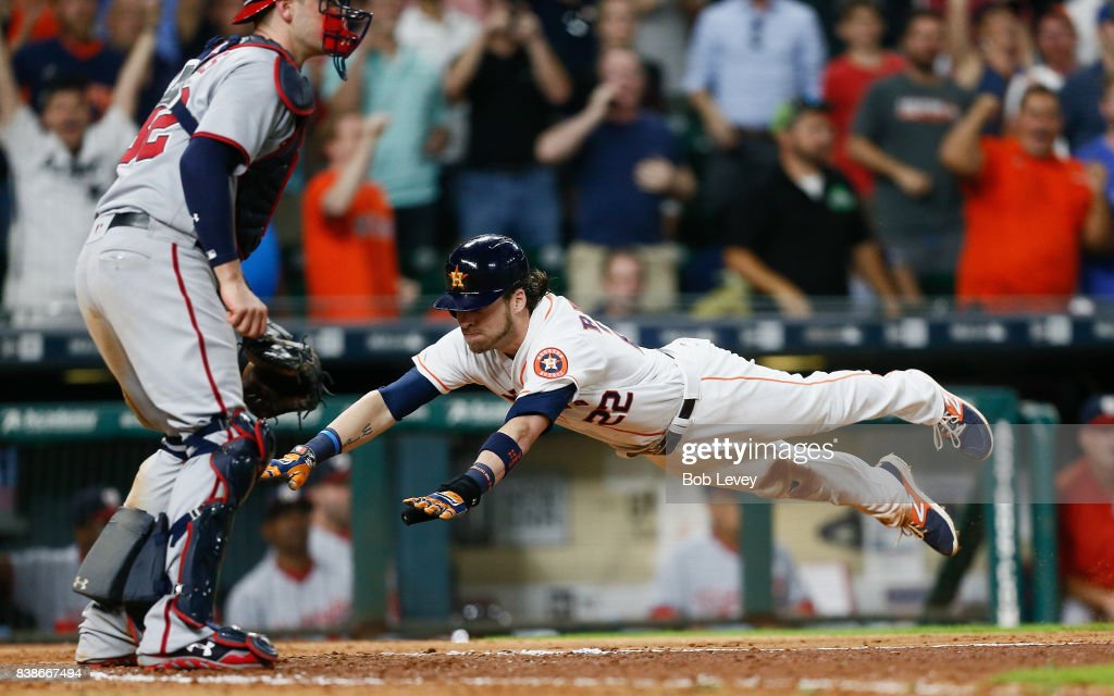 Josh Reddick #22 of the Houston Astros scores on a double by Yuli Gurriel #10 in the ninth inning against the Washington Nationals at Minute Maid Park on August 24, 2017 in Houston, Texas.