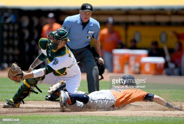 Josh Reddick of the Houston Astros scores sliding past Bruce Maxwell of the Oakland Athletics in the top of the first inning at Oakland Alameda...