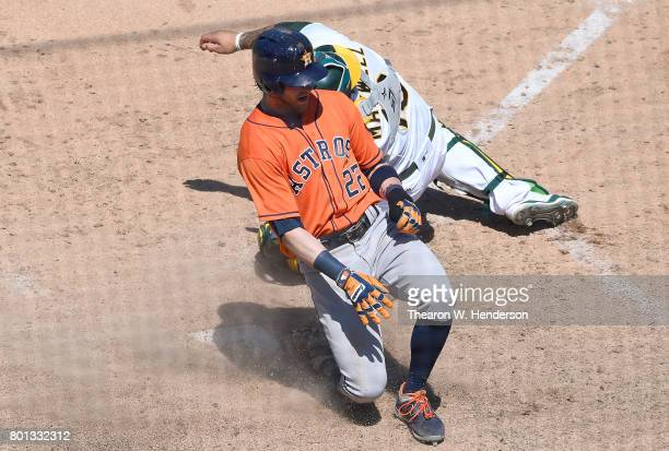 Josh Reddick of the Houston Astros scores sliding past Bruce Maxwell of the Oakland Athletics in the top of the eighth inning at Oakland Alameda...