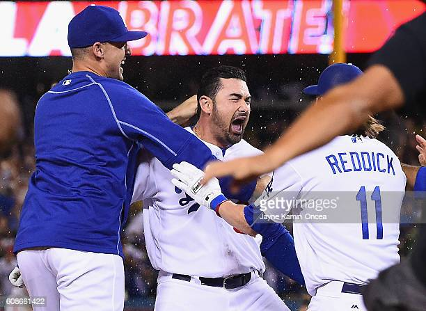 Josh Reddick of the Los Angeles Dodgers and Trayce Thompson celebrate after Adrian Gonzalez got a walk off double in the ninth inning of the game to...