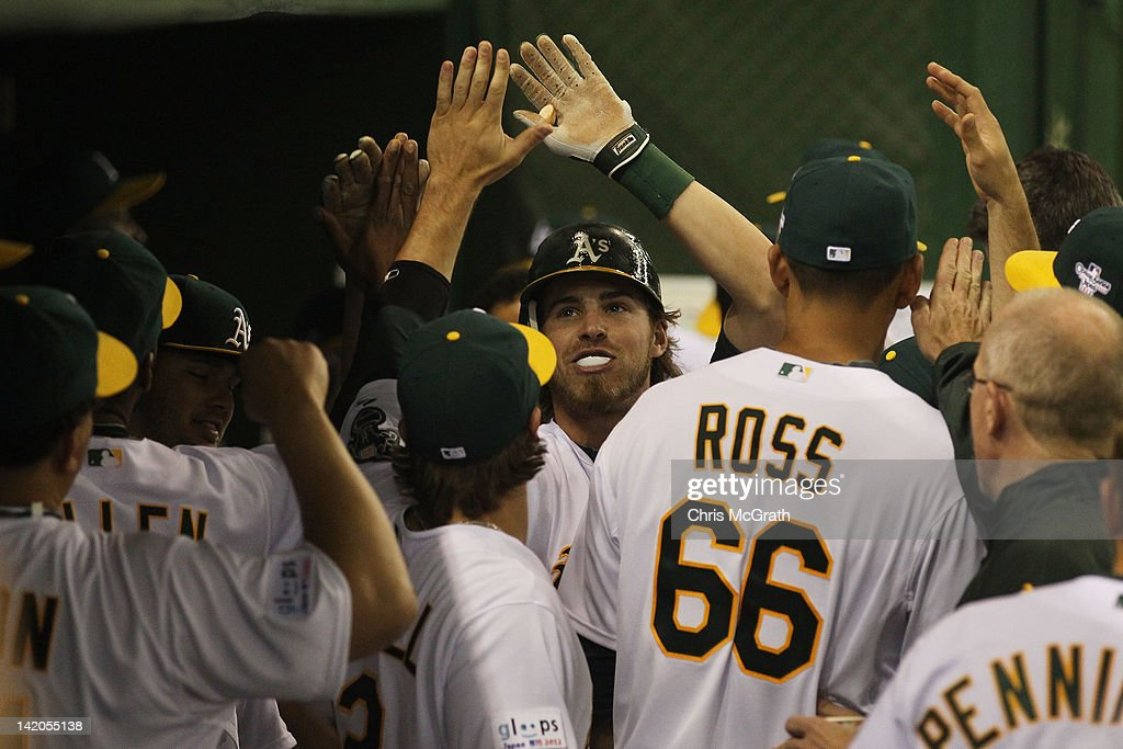 <a gi-track='captionPersonalityLinkClicked' href=/galleries/search?phrase=Josh+Reddick&family=editorial&specificpeople=5746348 ng-click='$event.stopPropagation()'>Josh Reddick</a> #16 of the Oakland Athletics celebrates with team mates after hitting a home run in the seventh inning against the Seattle Mariners during the MLB Opening Series game two between the Seattle Mariners and Oakland Athletics at Tokyo Dome on March 29, 2012 in Tokyo, Japan.