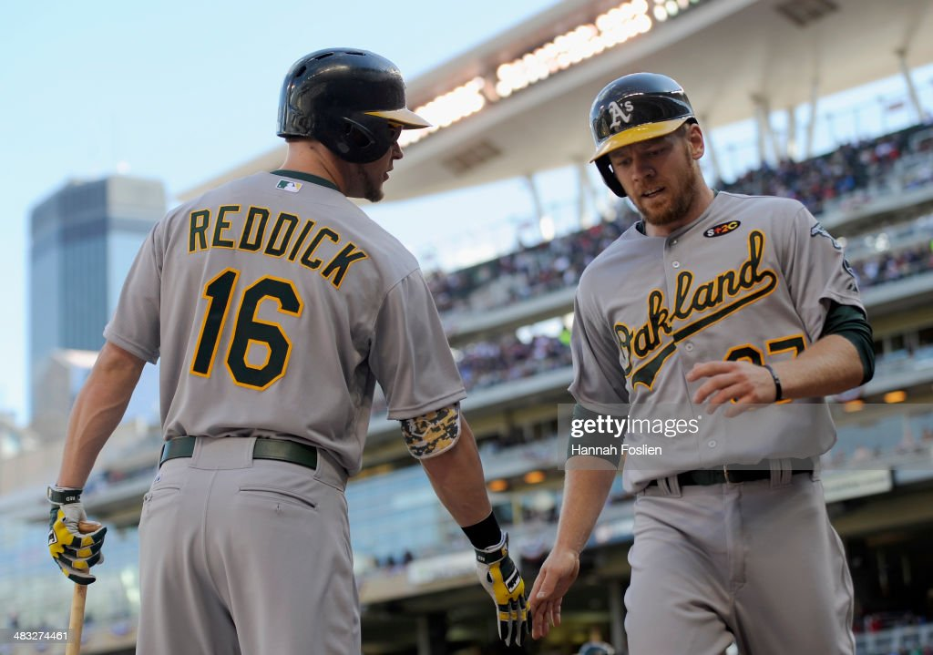 <a gi-track='captionPersonalityLinkClicked' href=/galleries/search?phrase=Josh+Reddick&family=editorial&specificpeople=5746348 ng-click='$event.stopPropagation()'>Josh Reddick</a> #16 of the Oakland Athletics congratulates teammate <a gi-track='captionPersonalityLinkClicked' href=/galleries/search?phrase=Brandon+Moss&family=editorial&specificpeople=702783 ng-click='$event.stopPropagation()'>Brandon Moss</a> #37 of the Oakland Athletics on scoring a run against the Minnesota Twins during the second inning of the home opening game on April 7, 2014 at Target Field in Minneapolis, Minnesota. The Athletics defeated the Twins 8-3.