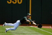 Josh Reddick of the Oakland Athletics dives but can't make the catch of this ball that goes for a doube off the bat of Jose Altuve of the Houston...