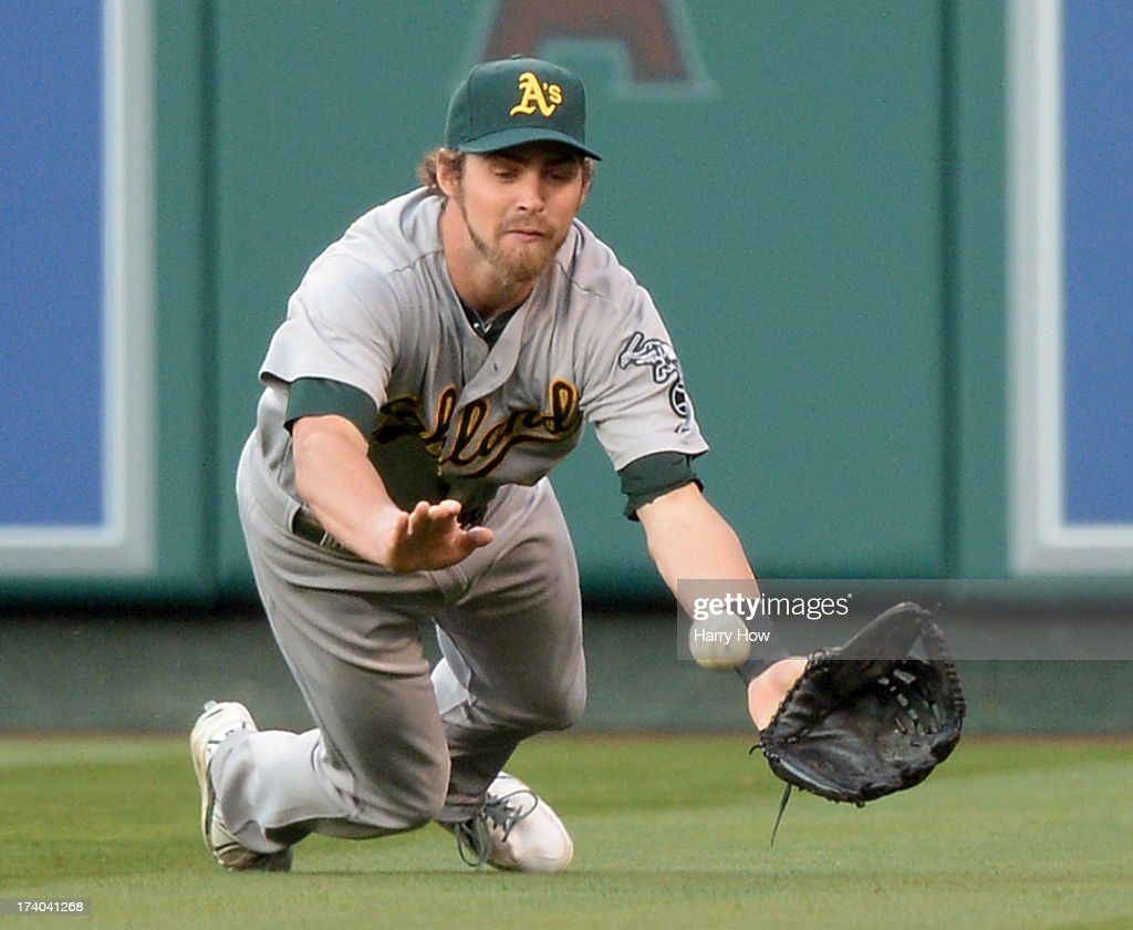 Josh Reddick #16 of the Oakland Athletics dives for a Josh Hamilton #32 of the Los Angeles Angels double to score a run for a 1-0 lead during the first inning at Angel Stadium of Anaheim on July 19, 2013 in Anaheim, California.