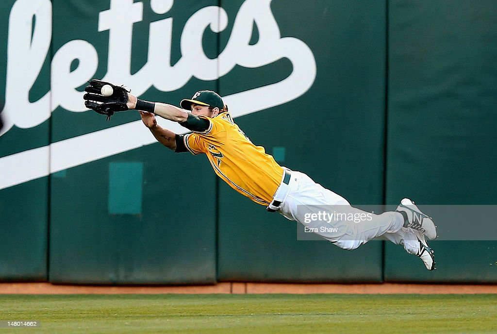 Josh Reddick #16 of the Oakland Athletics dives to catch a ball hit by <a gi-track='captionPersonalityLinkClicked' href=/galleries/search?phrase=Ichiro+Suzuki&family=editorial&specificpeople=201556 ng-click='$event.stopPropagation()'>Ichiro Suzuki</a> #51 of the Seattle Mariners in the third inning at O.co Coliseum on July 7, 2012 in Oakland, California.